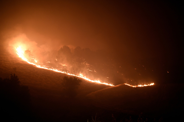 Winters, California, U.S. - Fire crews worked through the night trying to get control on the wind-driven Quail Fire near Winters California. The fire continued to move quickly and showed erratic and dangerous behavior making it hard for firefighters to get control.