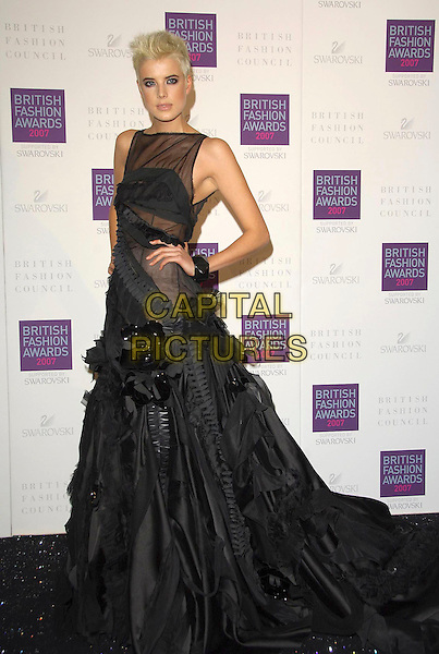 AGYNESS DEAN.Arriving at the British Fashion Awards 2007 at the Horticulutral Hall London, Engalnd, .27th November  2007..full length black dress gown hand on hip.CAP/CAS.©Bob Cass/Capital Pictures.
