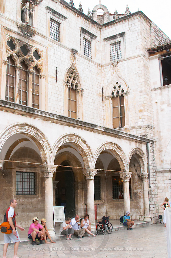 Tourists sitting on the arched porch in front of the Sponza palace on the Luza Lodge Loggia Square Dubrovnik, old city. Dalmatian Coast, Croatia, Europe.