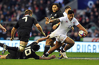 Manu Tuilagi looks to get past Dan Carter. QBE International match between England and New Zealand on December 1, 2012 at Twickenham Stadium in London, England. Photo by: Patrick Khachfe / Onside Images
