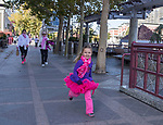 A young girls runs along the river walk during the Susan G. Koman Race for the Cure in Reno, Nevada on Sunday, October 15, 2017.