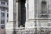 homeless person sleeping in window archway of church in Montreal