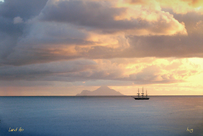 A sailboat passes in front of the distant island  of Saba