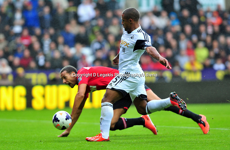 Swansea's Wayne Routledge takes a shot on goal after getting passed Rio Ferdinand.<br />