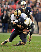 United States Navy Midshipmen quarterback Kriss Proctor (2) is tackled in the second quarter by a U.S.  Army Black Knight defender in the second quarter at FedEx Field in Landover, Maryland on Saturday, December 10, 2011.  This was the 112th meeting of the two teams.  Navy won the game 27 - 21. .Credit: Ron Sachs / CNP