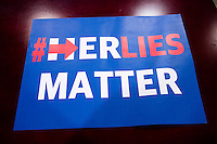 """A banner designed by John Paul Moran reading """"#HerLiesMatter,"""" in reference to Hillary Clinton, lays on a desk in his live/work studio in Boston, Massachusetts. Moran is a Trump supporter who will be traveling to Washington DC to attend the inauguration and associated events as Donald Trump is sworn in as president of the United States. Moran volunteered with the Trump campaign in Massachusetts and helped organize rallies around his """"#HerLiesMatter"""" campaign."""
