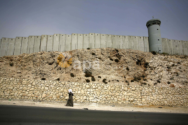 A Palestinian woman walks past the Israeli separation barrier near the West Bank town of Al-Ram on Sept. 26, 2010. Israel says the barrier is needed for security, but Palestinians consider it a land grab. Photo by Eyad Jadallah