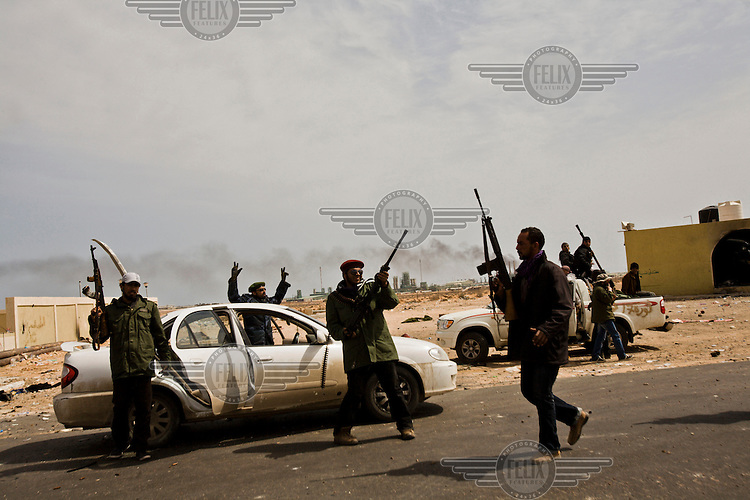 Rebels celebrate retaking the important oil town of Ras Lanuf, with the huge refinery seen in the background.  On 17 February 2011 Libya saw the beginnings of a revolution against the 41 year regime of Col Muammar Gaddafi.