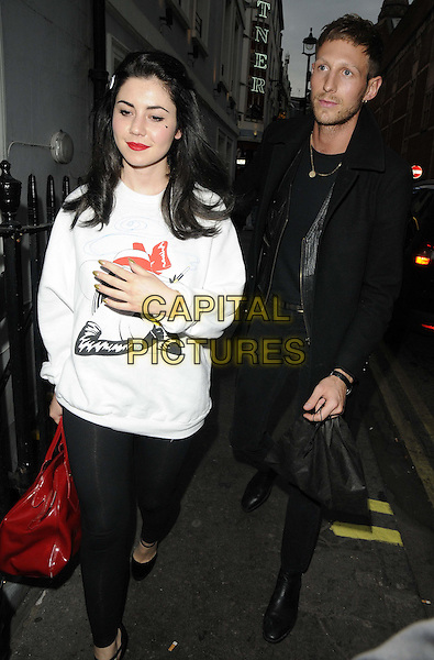 Marina Diamandis of Marina and the Diamonds & guest.The Claire's e-commerce site launch party, Kettners bar & restaurant, London, England..April 24th, 2013.full length black jacket jeans denim white leggings sweatshirt .CAP/CAN.©Can Nguyen/Capital Pictures.