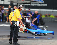 Jun 19, 2015; Bristol, TN, USA; NHRA A member of the Safety Safari blows off debris in the burnout area using a leaf blower during qualifying for the Thunder Valley Nationals at Bristol Dragway. Mandatory Credit: Mark J. Rebilas-