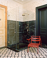 A walk-in shower is contained in a transparent glass box and lined in glamorous black-and-white marble in pleasing contrast to rough brick walls above