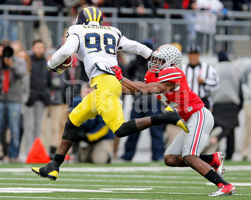 Ohio State Buckeyes cornerback Doran Grant (12) pushes Michigan Wolverines quarterback Devin Gardner (98) during the fourth quarter of the NCAA football game against Michigan at Ohio Stadium on Saturday, November 29, 2014. (Columbus Dispatch photo by Jonathan Quilter)