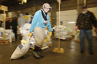 Wednesday, February 13, 2013.  Volunteer Diane Toebe drags a bag of musher's food drop bags to the appropriate  stack at Airland Transport in Anchorage.  Iditarod 2013.