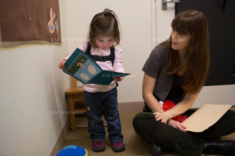 Melissa Kline (right), graduate student in the Department of Brain and Cognitive Sciences, works with Madeline Wilson in the Early Childhood Cognition Lab at MIT in Cambridge, Massachusetts, USA. Kline's research is looking at language usage and development in young children.  The goal in this experiment is to see what words Madeline uses to describe a situation indicated by pictures. The backpack worn by Madeline holds a microphone that records her speech during the experiment.