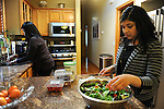 Debbie Tobar and daughter Bianca Tobar, 25, make dinner together in the kitchen of the family's house in the Bridgeport neighborhood in Chicago, Illinois on April 22, 2015.  Tobar works as an administrative assistant a doctor at a medical center.