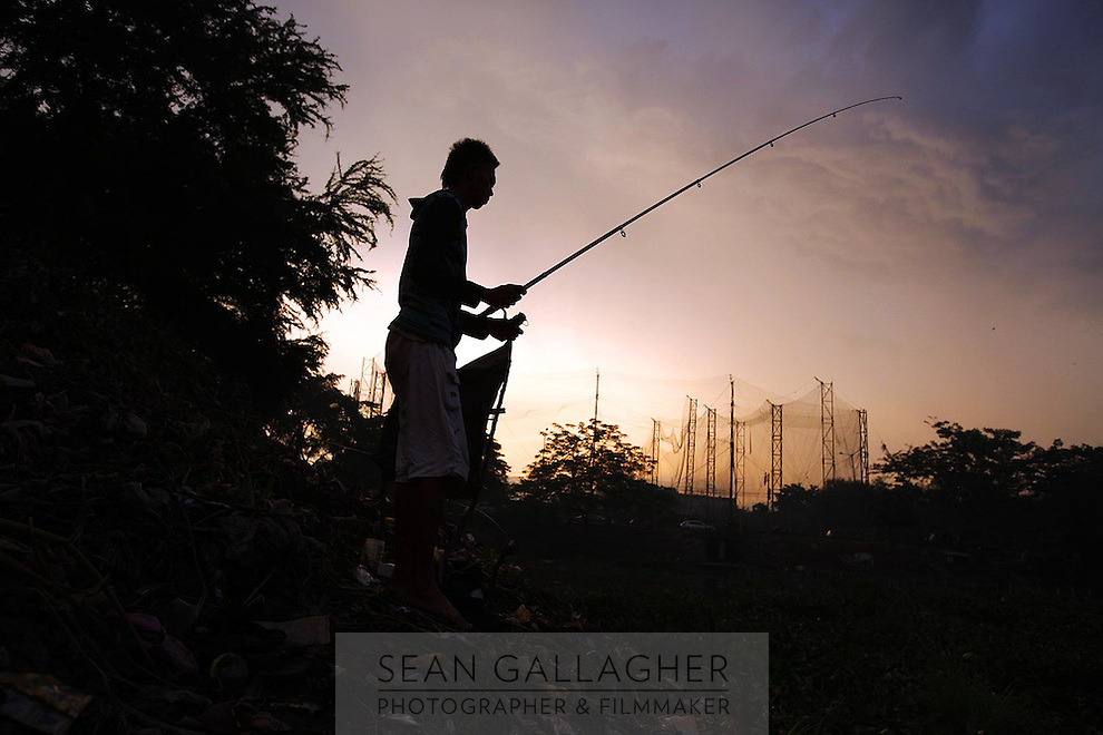 A man fishes at sunset.<br />