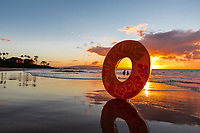 Two children playing in the water are framed by an inner tube at sunset, Wailea Beach, Maui.