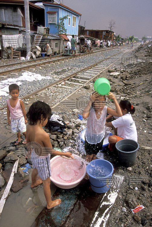 ©Caroline Penn/Panos Pictures..Philippines, Manila. Children washing from an illegal water connection beside rail tracks. Pandacan squatter settlement.