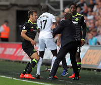 Cesar Azpilicueta of Chelsea (L) and manager of Chelsea, Antonio Conte (R) snatch the ball from Modou Barrow of Swansea City during the Premier League match between Swansea City and Chelsea at The Liberty Stadium on September 11, 2016 in Swansea, Wales.