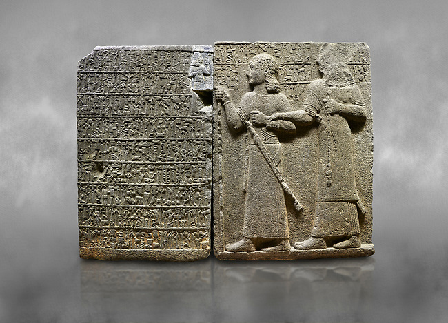"""Hittite monumental relief sculpted orthostat stone panel of Royal Buttress. Basalt, Karkamıs, (Kargamıs), Carchemish (Karkemish), 900-700 B.C. Anatolian Civilisations Museum, Ankara, Turkey.<br /> <br /> Hieroglyph panel (left) - Discourse of Yariris. Yariris presents his predecessor, the eldest son Kamanis, to his people. <br /> Right Panel - King Araras holds his son Kamanis from the wrist. King carries a sceptre in his hand and a sword at his waist while the prince leans on a stick and carries a sword on his shoulder. <br /> <br /> Hieroglyphs reads; """"This is Kamanis and his siblings. held his hand and despite the fact that he is a child, I located him on the temple. This is Yariris' image"""".  <br /> <br /> Against a grey art background."""