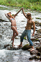 Young woman posing on rock in stream supported by shirtless man