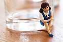 "A figure of ""Cup no Sococo"" with her leg trapped under a glass on August 19, 2014 in Tokyo, Japan. These mini figures are popular amongst young Japanese women who often use them when composing pictures of their lunch. The name Cup no Fuchiko translates to  or ""office lady, or OL, on the side of a cup"" and the figures are sold as drink ornaments. Made by  Kitan Club CO. LTD Cup no Fuchiko was created by the manga artist Katsuki Tanaka. There are currently 21 models of Cup no Fuchiko and Kitan Club has also made capsule toys from famous characters such as Street Fighter II, Moomin, Hello Kitty. (Photo by Rodrigo Reyes Marin/AFLO)"