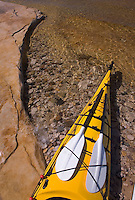 The stern of a sea kayak with spare paddles on sandstone ledge at Mosquito Beach in Pictured Rocks National Lakeshore near Munising, Michigan.