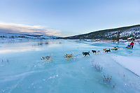 Musher crosses overflow on Ptarmigan creek near mile 101 checkpoint during the 1000 mile Yukon Quest sled dog race 2006, between Fairbanks, Alaska and Whitehorse, Yukon. Dubbed the toughest dogsled race in the world.