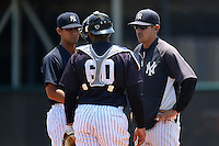GCL Yankees 1 pitcher Luis Cedeno (91), catcher Roybell Herrera (60), and pitching coach Cory Arbiso (46) meet on the mound during the first game of a doubleheader against the GCL Braves on July 1, 2014 at the Yankees Minor League Complex in Tampa, Florida.  GCL Yankees 1 defeated the GCL Braves 7-1.  (Mike Janes/Four Seam Images)