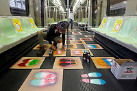 MEDELLÍN, COLOMBIA-MAY 4: Two urban artists make footprints with aerosol, so that passengers know where they should be on a train during the pandemic, COVID-19. on May 4, 2020, in Medellín, Colombia. The physical distance and the maximum occupancy of 35% of the public transport system, a requirement of the National Government, as a preventive measure to stop the spread of COVID-19 (Photo by Fredy Builes/VIEWpress)