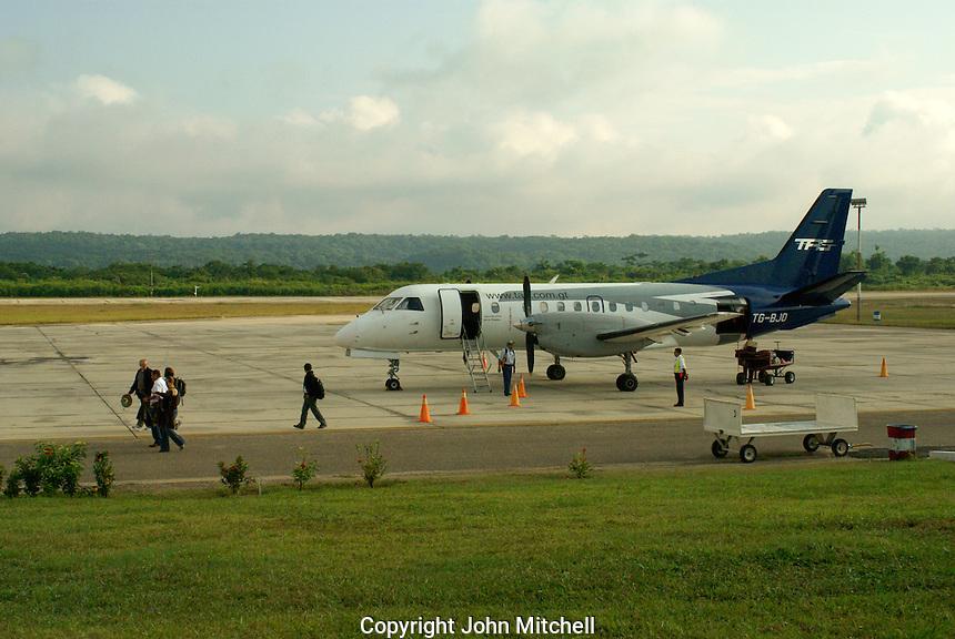 Passengers getting off a prop plane at the Santa Elena Airport or Mundo Maya Airport, El Peten, Guatemala