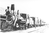 3/4 fireman's-side view of C&amp;S #5 heading a passenger train at a station.  The engineer is oiling around while another person looks on.<br /> C&amp;S  Como, CO
