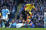 Gabriel Agbonlahor of Aston Villa jumps over a tackle by Nicolas Otamendi of Manchester City - Barclay's Premier League - Manchester City vs Aston Villa - Etihad Stadium - Manchester - 05/03/2016 Pic Philip Oldham/SportImage
