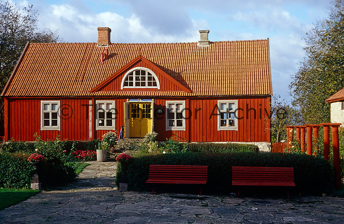 The exterior woodwork of this charming house in the Swedish countryside has been painted a deep russet red