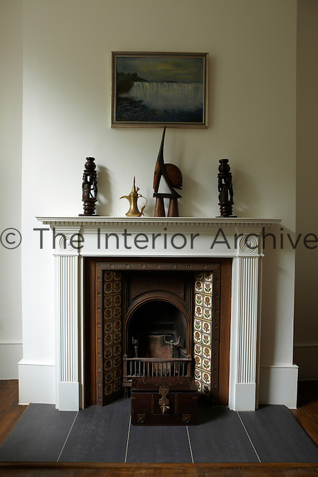 A Victorian style fireplace with a white surround and tiled grate. Objects are displayed on the mantelpiece and a wooden box is placed on the slate hearth.