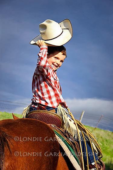 Young cowboy on horseback tips his hat,  San Luis Obispo, California