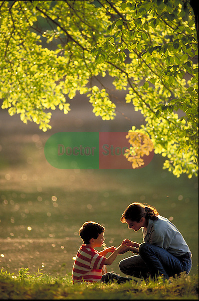 woman playing in park with young boy
