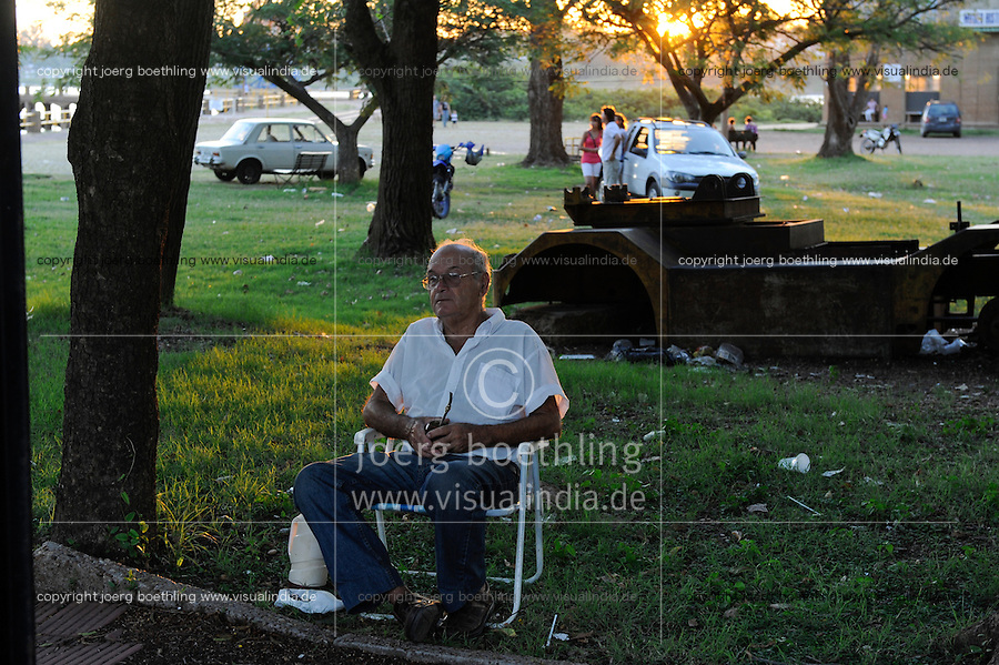 URUGUAY Salto, man with Mate tea at Rio uruguay in the evening