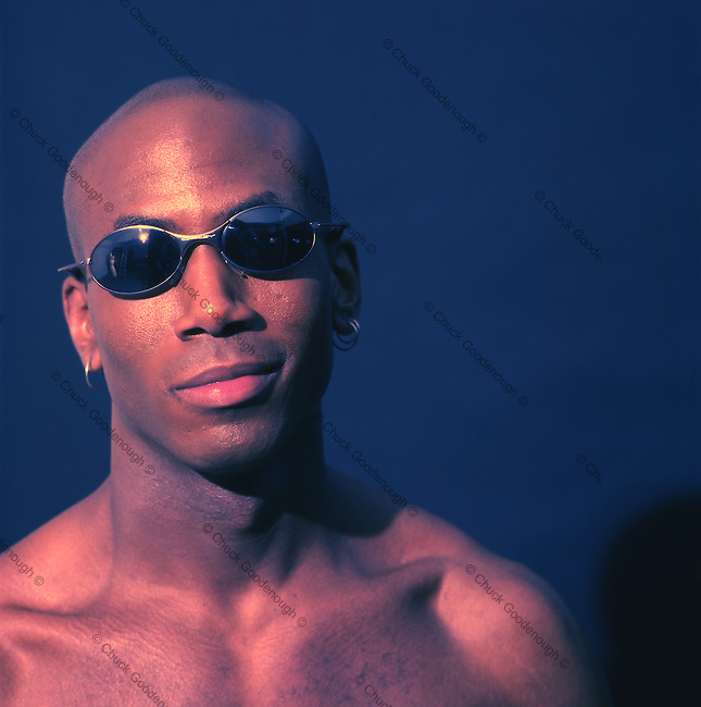 Photo of a Smiling African American Bald Man with Sunglasses and several Earrings