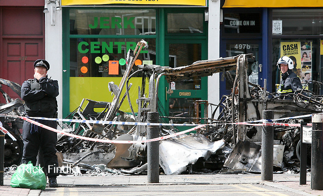 PH: Rick Findler..07.08.11 A tired policeman stands infront of a burnt out double decker bus which was sewt alight last night during the rioting that saw 26 officers injured. The violence was sparked by the fatal shooting of Mark Duggan by a police officer on thursday night.