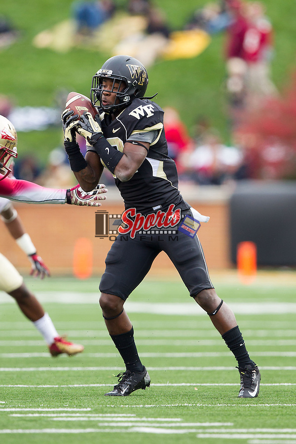 Tyree Harris (12) of the Wake Forest Demon Deacons attempts to catch a pass during second half action against the Florida State Seminoles at BB&T Field on November 9, 2013 in Winston-Salem, North Carolina.  The Seminoles defeated the Demon Deacons 59-3.  (Brian Westerholt/Sports On Film)