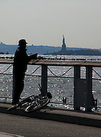 Man fishing and smoking from a pier with the statue of Liberty in the backgrounnd, New York. USA.