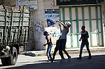 Palestinians hurl stones at Israeli troops after the troops shot dead two Palestinians, Marwan Kawasme and Amar Abu Aysha, in the West Bank city of Hebron September 23, 2014. Israeli troops shot dead the two Palestinians in the West Bank city of Hebron on Tuesday and the military said they were members of Hamas responsible for the killing of three Israeli youths in June, an attack that led to the Gaza war. Kawasme and Abu Aysha, both in their 30s, were shot dead during a gun battle after Israeli troops surrounded a house in the city before dawn, the army and residents said. Israel had been hunting the men for three months. Photo by Mamoun Wazwaz