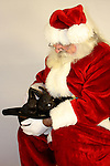 Santa Claus holding two black bunnies in a cowboy hat