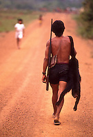 Daily life at Trans Amazonian highway near Novo Repartimento city, hunter with shot-gun carries dead monkey. Para State, Brazil.
