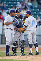 Jack Lopez (11) of the Wilmington Blue Rocks helps translate for catcher Cam Gallagher (35) as he talks to starting pitcher Miguel Almonte (27) during the game against the Winston-Salem Dash at BB&T Ballpark on April 3, 2014 in Winston-Salem, North Carolina.  The Blue Rocks defeated the Dash 3-1.  (Brian Westerholt/Four Seam Images)