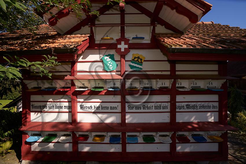 A traditional chalet apiary at the Bregensdorf farm. First cited in 1315, the farm has housed basket hives for centuries. Beekeeping is a complementary activity for the Fisch family.<br /> &quot;Take the example of the hardworking bees, it is only through work that benediction comes&quot;.<br /> Un rucher ch&acirc;let traditionnel &agrave; la ferme de Bregensdorf. Mention&eacute;e pour la premi&egrave;re fois en 1315, la ferme a abrit&eacute; des ruches panniers pendant des si&egrave;cles. L&rsquo;apiculture est un compl&eacute;ment pour la famille Fisch.<br /> &laquo; Prends l&rsquo;exemple des abeilles laborieuses, c&acute;est seulement par le travail que vient la b&eacute;n&eacute;diction &raquo;.