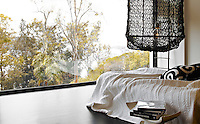 Black netting lamps hang either side of a low-slung bed in the bedroom which has stunning views over Pittwater and Scotland Island