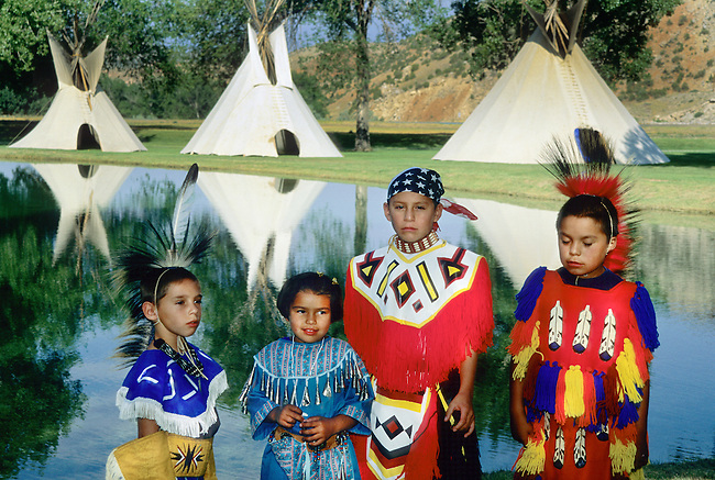 Native American family of cousins dressed in traditional regalia in front of lake with tipis during the Gift of the Waters Pageant in Thermopolis Wyoming