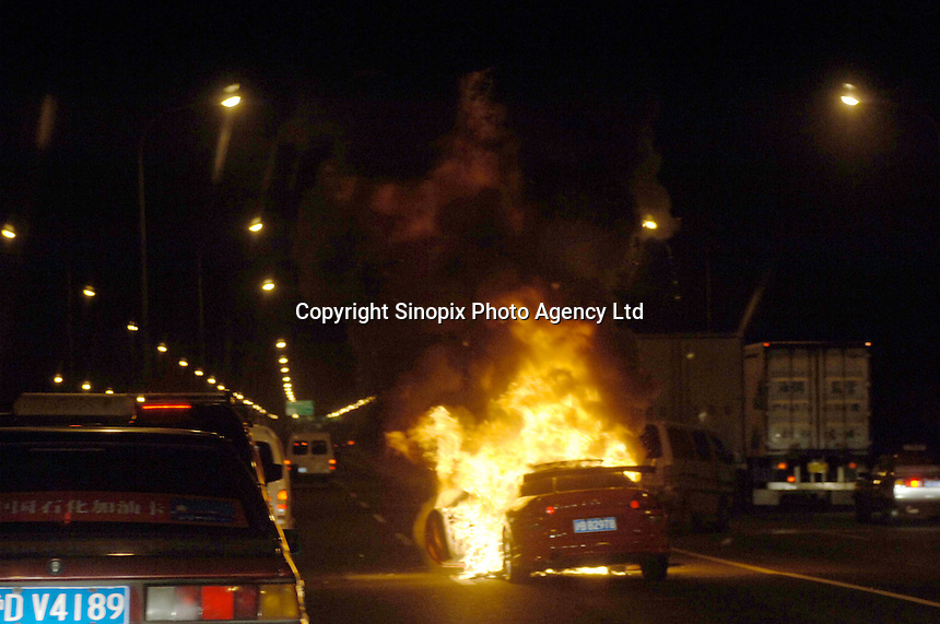 A car burns on the road in Shanghai, China..